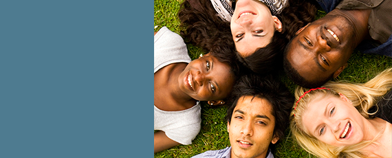 Photo of group of a circle of young people lying on the grass smiling
