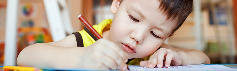 Close up image of young child coloring with marker