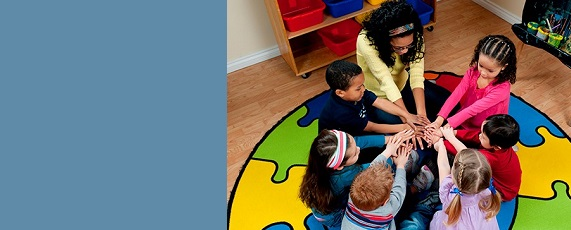 Photo of toddlers playing on colorful rug-social emotional learning and approaches to play
