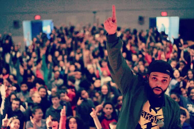 man holding one finger raised over his head, standing in front of an assembly of students